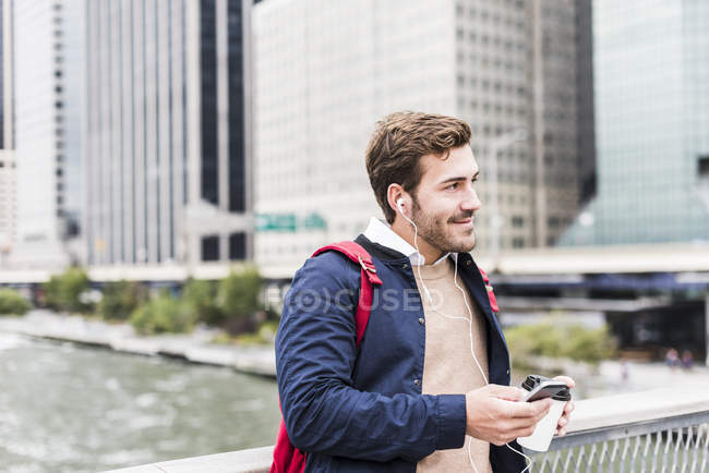 Hombre de negocios en Manhattan sosteniendo teléfonos inteligentes y auriculares, Ciudad de Nueva York, Estados Unidos - foto de stock