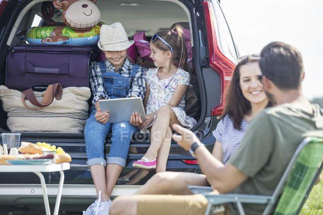 Счастливая семья в дороге, отдыхающая на обочине дороги — стоковое фото