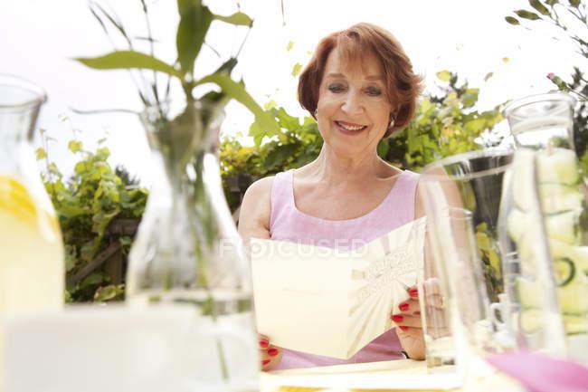 Senior woman sitting in garden, holding birthday card — Stock Photo