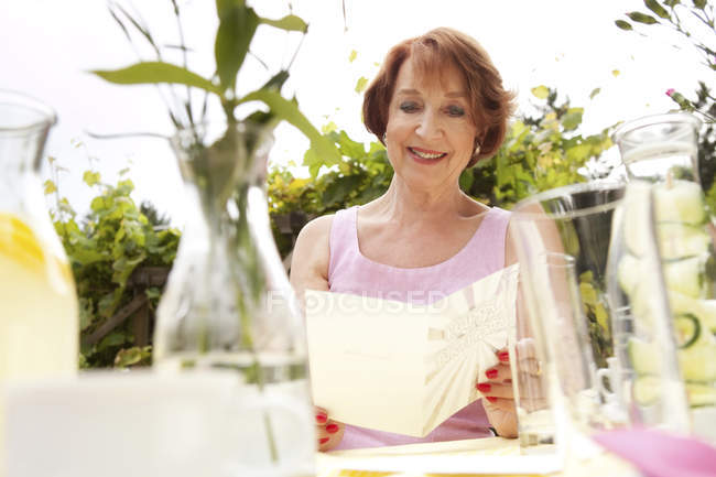 Senior woman sitting in garden, holding birthday card — Stock Photo