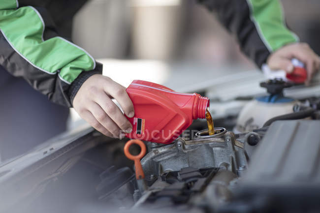 Man filling up car with motor oil — Stock Photo