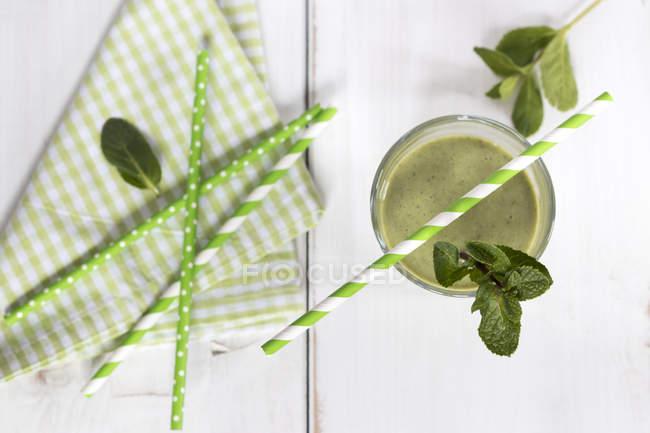 Вид зверху зелений льстец з питною соломкою і Листя м'яти — стокове фото