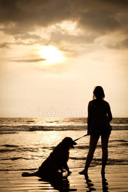 Mexico, Nayarit, silhouette of young woman with her dog on a leash at a beach at sunset — Stock Photo