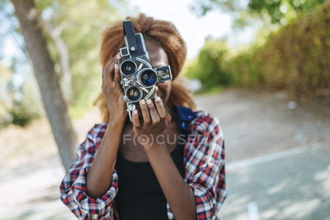 Young woman filming with an old-fashioned camera — Stock Photo