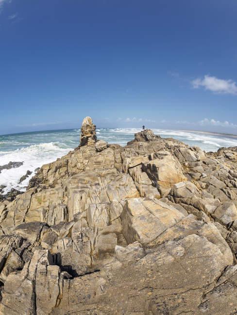 Francia, Bretaña, Finisterre, hombre de pie en la costa atlántica - foto de stock