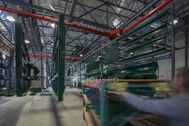 Cape Town, Sud Africa, lavoratori che spinge carrello con grandi parti in fattore di produzione camion d'acciaio — Foto stock