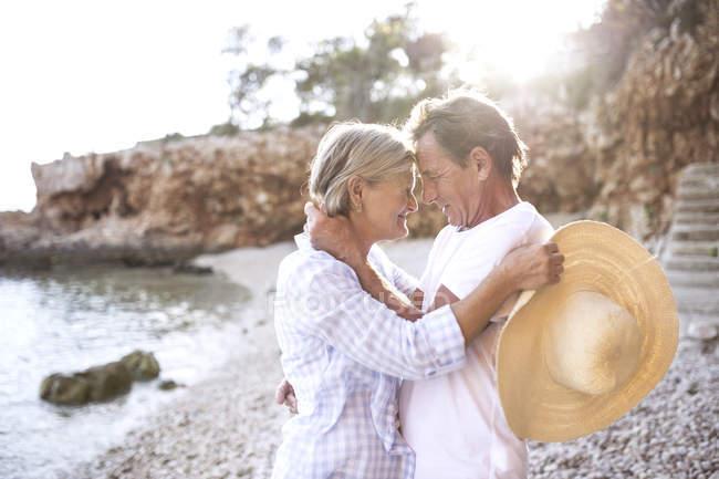 Aktiv süß senior pärchen umarmung auf strand — Stockfoto