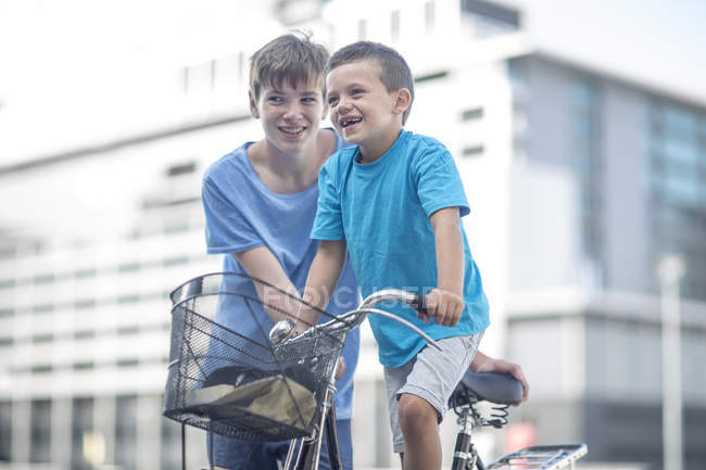 Boy teaching little brother how to ride a bicycle — Stock Photo