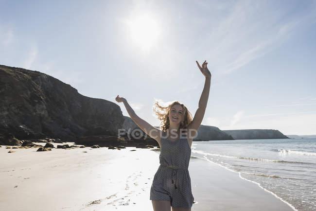 Glücklich Teenager-Mädchen mit erhobenen Armen am Strand — Stockfoto