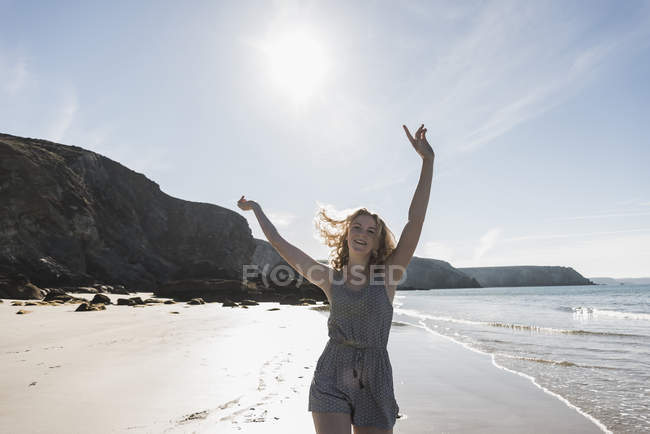 Happy teenage girl with raised arms on the beach — Stock Photo