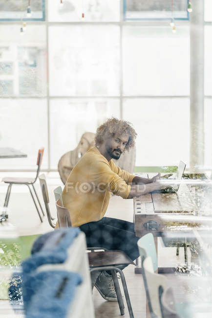 Young man sitting at table and working with laptop behind windowpane — Stock Photo