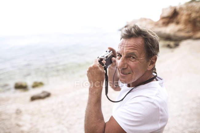 Portrait of senior man taking pictures on the beach — Stock Photo