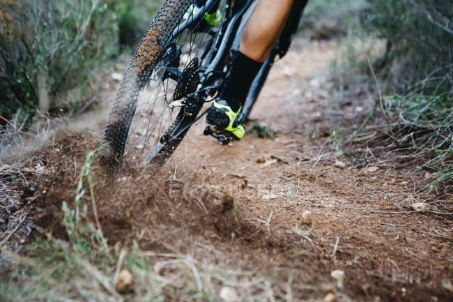 Close-up of mountainbiker skidding in a curve — Stock Photo