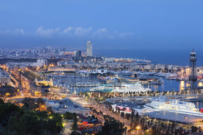 Spain, Barcelona, view to the lighted city at twilight — Stock Photo