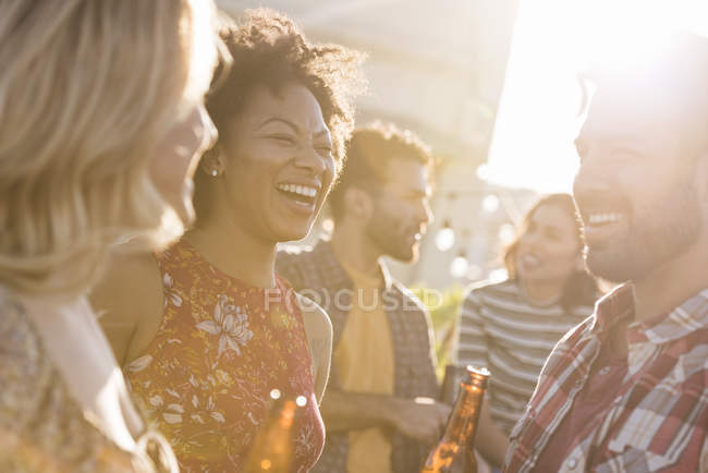 Friends at rooftop party in bright sunshine day — Stock Photo