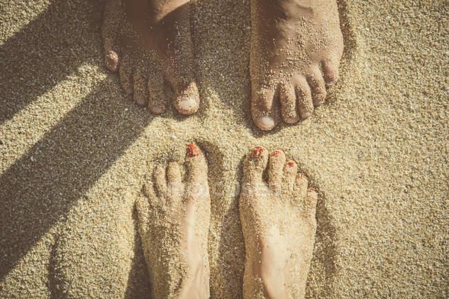 Ноги пары, стоящей на песке, видны сверху — стоковое фото