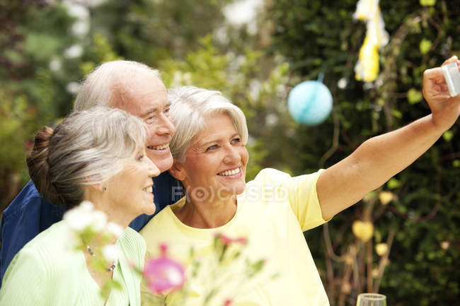 Happy senior man taking selfie with guests at garden — Stock Photo