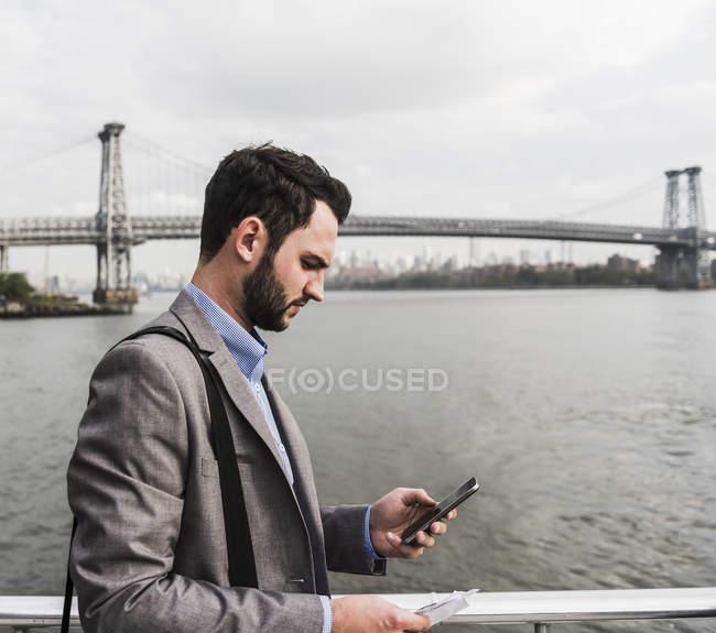 Hombre de negocios en ferry en East River comprobando el teléfono celular, Ciudad de Nueva York, Estados Unidos - foto de stock