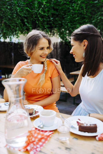 Two young women drinking coffee at outdoor cafe — Stock Photo
