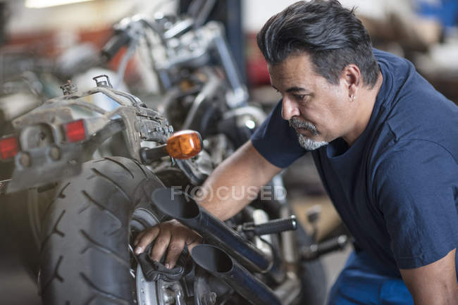 Concentrated motorcycle mechanic working in workshop — Stock Photo