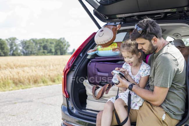 Батько і дочка, сидячи в відкрити завантаження автомобіля, дивлячись на камеру — стокове фото