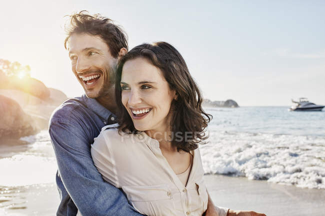 Happy adult couple hugging on the beach — Stock Photo