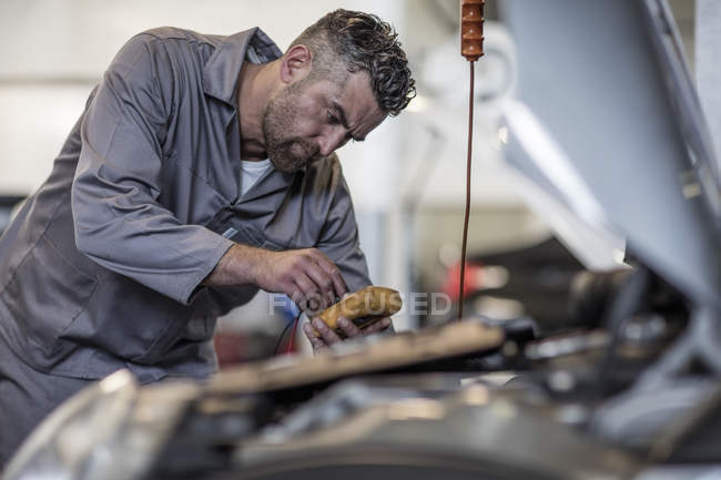 Car mechanic in a workshop using diagnostic equipment — Stock Photo
