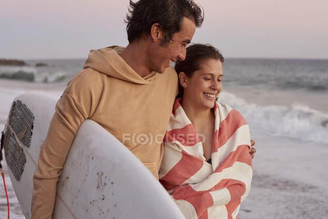 Усміхаючись молода пара на пляжі, несучи для серфінгу — стокове фото