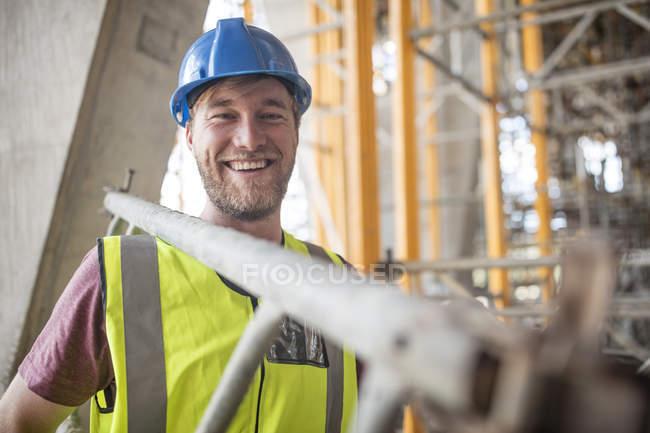 Bauarbeiter auf Baustelle trägt Leiter — Stockfoto