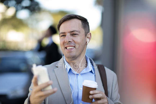 Businessman with cell phone listening to music — Stock Photo