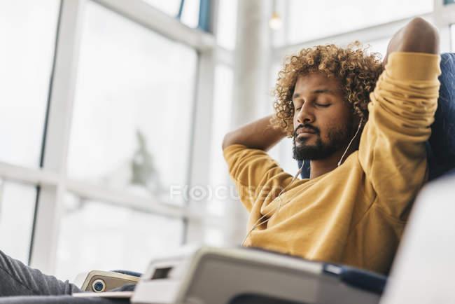 Jeune homme relaxant dans un fauteuil avec les yeux fermés et utilisant des écouteurs — Photo de stock