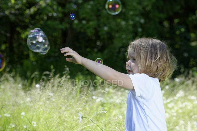Little girl trying to catch soap bubbles on a meadow — Stock Photo