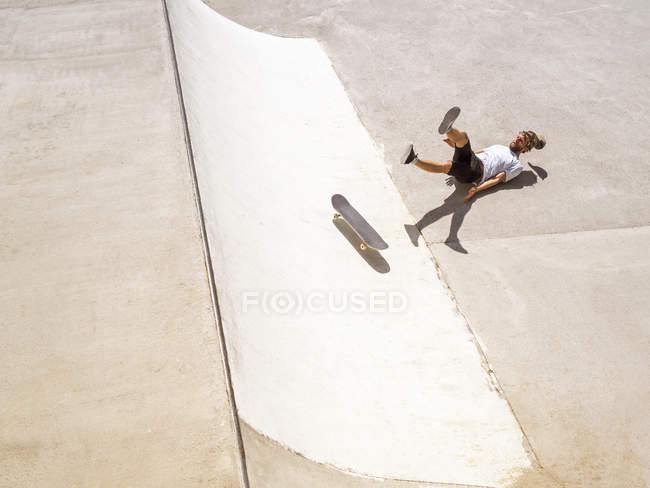 Young man falling with skateboard in skate park — Stock Photo