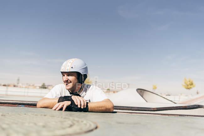 Lächelnder Mann in Helm stützte sich auf Ramp Skate Park — Stockfoto