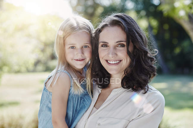 Portrait of smiling mother with daughter in garden — Stock Photo