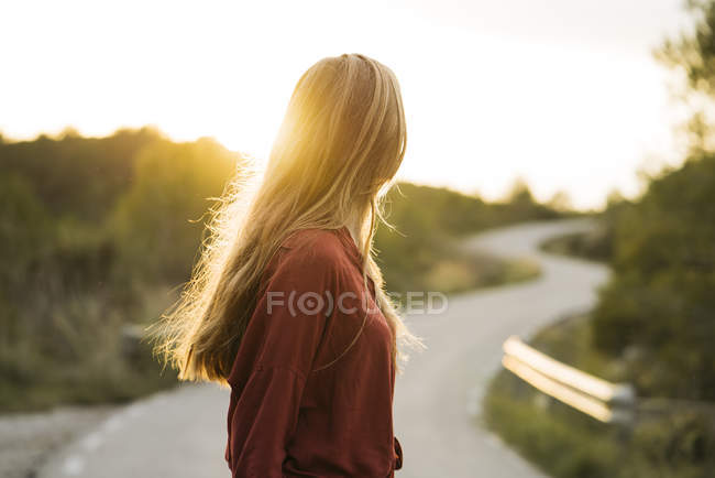 Young blond woman standing at backlit and looking away — Stock Photo