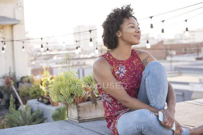 Жінка, сидячи на даху дивлячись сторону — стокове фото