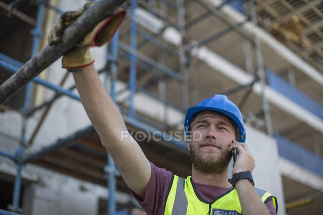 Construction worker on construction site talking on the phone — Stock Photo