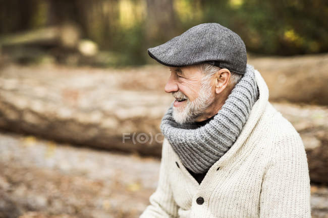 Happy senior man wearing cap and polo neck — Stock Photo