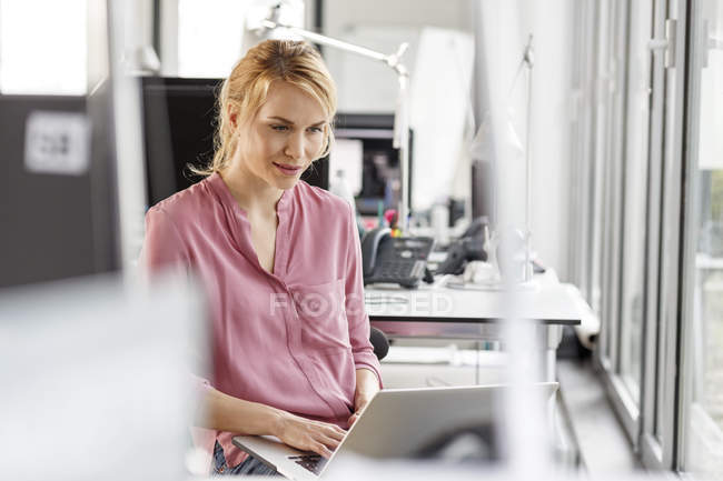 Caucasian woman using laptop in office — Stock Photo