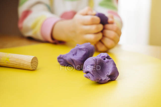 Child's hands kneading modelling clay — Stock Photo
