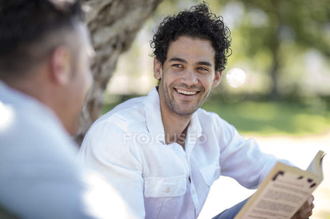 Cape Town, South Africa,Young male seated outside garden with friend reading book — Stock Photo