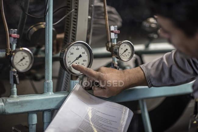 Caucasian man checking pressure on machine — Stock Photo