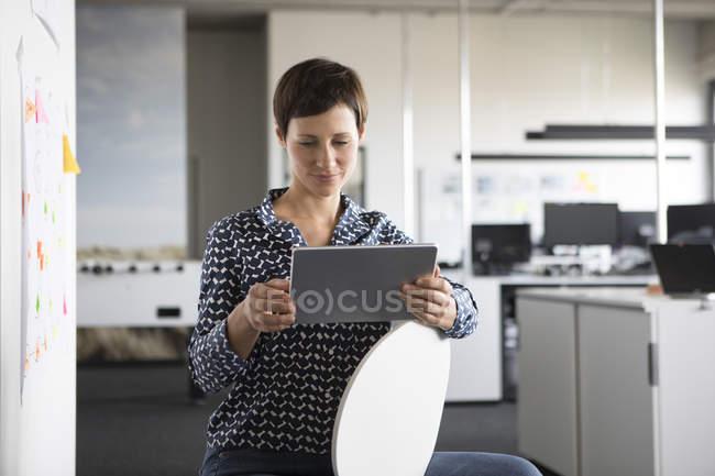 Femme d'affaires confiante en utilisant la tablette au bureau — Photo de stock