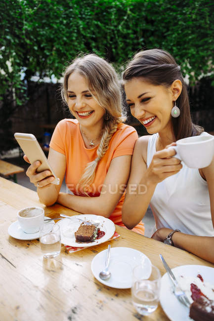 Two young women with cell phone picture at outdoor cafe — Stock Photo