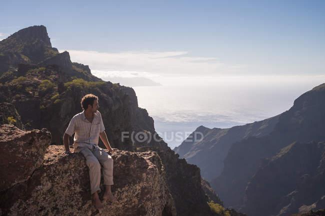 España, Tenerife, las montañas de Teno, Masca, hombre sentado en el acantilado - foto de stock