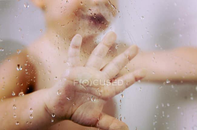 Hand of little boy against wet glass pane in shower — Photo de stock