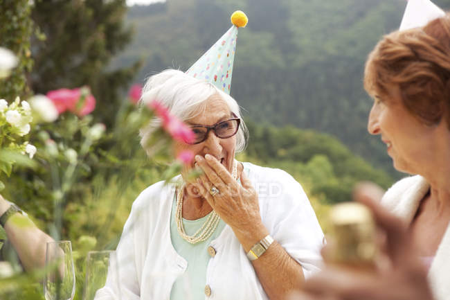 Senior ladies laughing at celebration, wearing party hats — Stock Photo