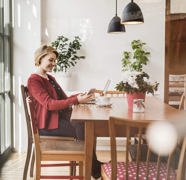 Smiling young woman with cell phone and laptop sitting in a cafe — Stock Photo