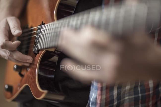Primer plano de hombre tocando guitarra eléctrica - foto de stock